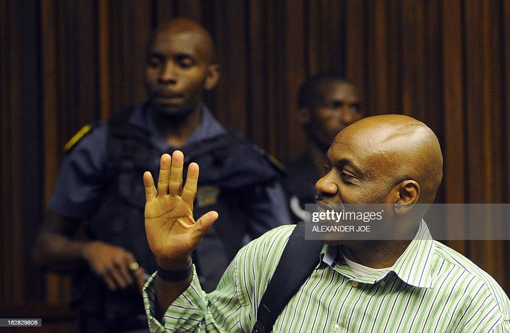 Nigerian militant leader Henry Okah greets his family in court after his case was posted because he changed his legal team at Johannesburg High Court on February 28, 2013. Okah is convicted of 13 terrorism charges, including the 2010 independence day bombings in Abuja. Okah was found guilty of masterminding attacks including twin car bombings in Abuja on October 1, 2010, and two explosions in March 2010 in the southern Nigerian city of Warri, a major hub of the oil-rich Delta region. He faces a minimum term of life in prison. AFP PHOTO / ALEXANDER JOE