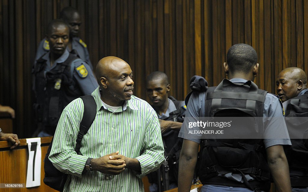 Nigerian militant leader Henry Okah (L) is escorted by South African police after his case was posted because he changed his legal team at Johannesburg High Court on February 28, 2013. Okah is convicted of 13 terrorism charges, including the 2010 independence day bombings in Abuja. Okah was found guilty of masterminding attacks including twin car bombings in Abuja on October 1, 2010, and two explosions in March 2010 in the southern Nigerian city of Warri, a major hub of the oil-rich Delta region. He faces a minimum term of life in prison.