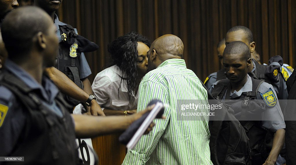Nigerian militant leader Henry Okah (C) kisses his wife Azuka in the courtroom after his case was posted because he changed his legal team at Johannesburg High Court on February 28, 2013. Okah is convicted of 13 terrorism charges, including the 2010 independence day bombings in Abuja. Okah was found guilty of masterminding attacks including twin car bombings in Abuja on October 1, 2010, and two explosions in March 2010 in the southern Nigerian city of Warri, a major hub of the oil-rich Delta region. He faces a minimum term of life in prison.