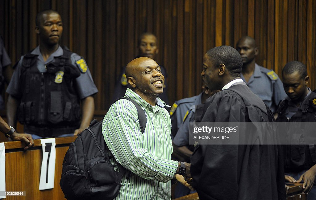 Nigerian militant leader Henry Okah (L) shakes hands with his former attorney Lucky Maunatlala in the courtroom after his case was posted because he changed his legal team at Johannesburg High Court on February 28, 2013. Okah is convicted of 13 terrorism charges, including the 2010 independence day bombings in Abuja. Okah was found guilty of masterminding attacks including twin car bombings in Abuja on October 1, 2010, and two explosions in March 2010 in the southern Nigerian city of Warri, a major hub of the oil-rich Delta region. He faces a minimum term of life in prison. AFP PHOTO / ALEXANDER JOE