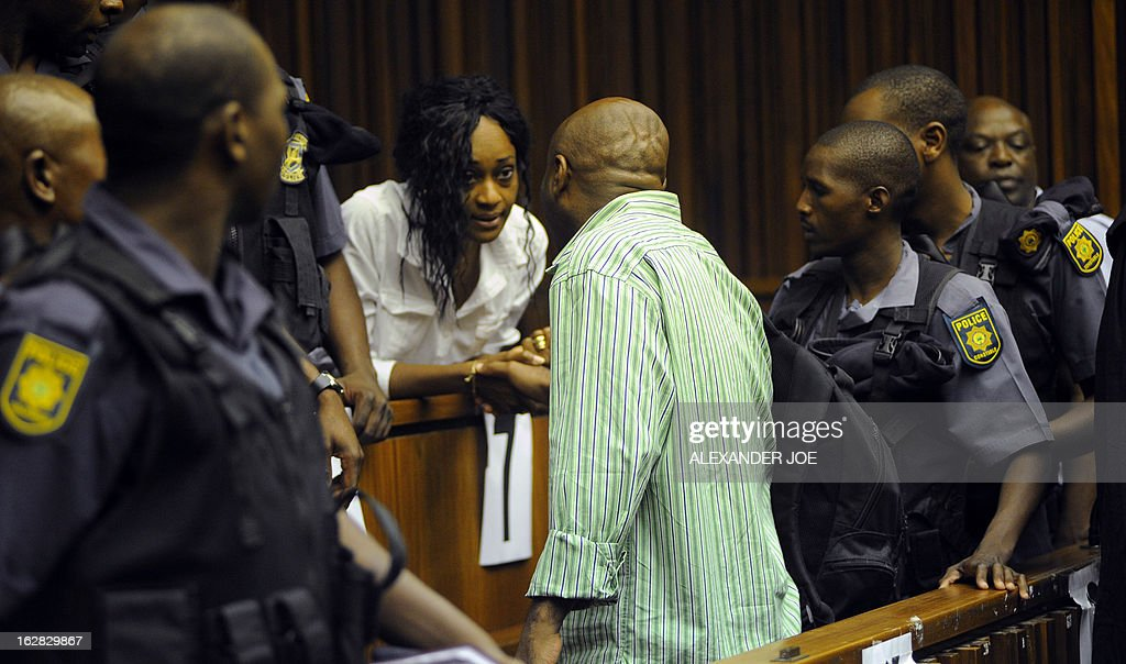 Nigerian militant leader Henry Okah (C) speaks to his wife Azuka in the courtroom after his case was postponed because he changed his legal team at Johannesburg High Court on February 28, 2013. Okah is convicted of 13 terrorism charges, including the 2010 independence day bombings in Abuja. Okah was found guilty of masterminding attacks including twin car bombings in Abuja on October 1, 2010, and two explosions in March 2010 in the southern Nigerian city of Warri, a major hub of the oil-rich Delta region. He faces a minimum term of life in prison.