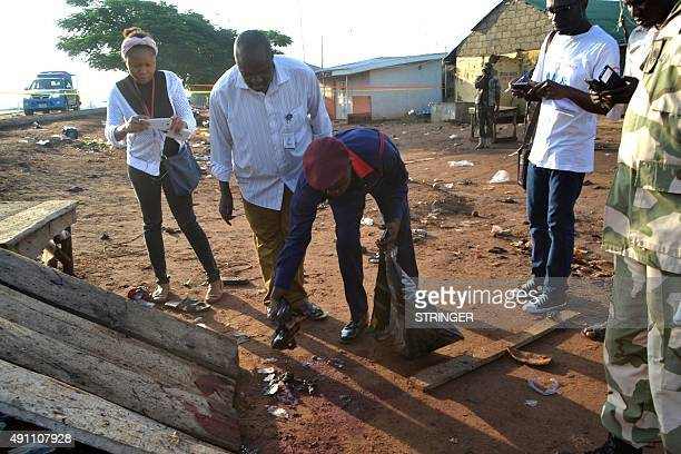 Nigerian official collects clues and parts of the victims in Nyanya near Abuja on October 3 after two bomb blasts ripped through the outskirts of...
