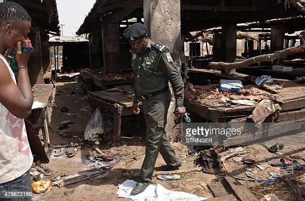 A Nigerian policeman inspects the site of a suicide attack at a busy cattle market in the northeastern Nigerian city of Maiduguri on June 2 2015 At...