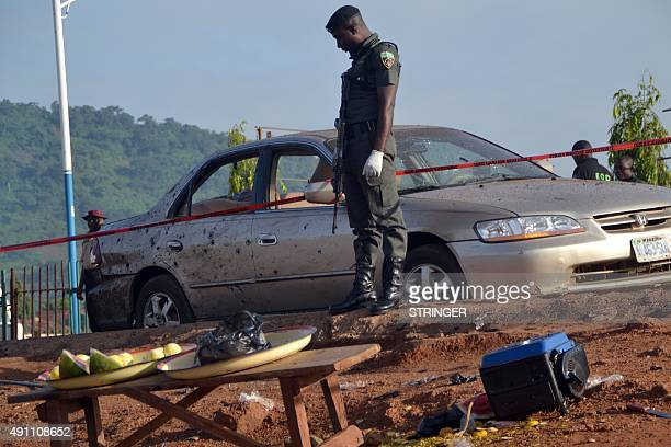 A Nigerian policeman stands beside a damaged car in Nyanya near Abuja on October 3 after two bomb blasts ripped through the outskirts of Nigeria's...