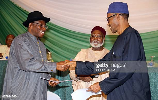Nigerian President Goodluck Jonathan and APC main opposition party's presidential candidate Mohammadu Buhari shake hands under the eyes of Chairman...