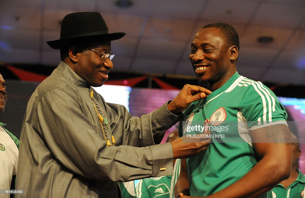 Nigerian President Goodluck Jonathan decorates the assistant national football Coach Daniel Amoakachi (R) with national award during the presidential banquet in honour of the victorious team in Abuja February 12, 2013. The newly crowned African champions Nigerian Super Eagles arrives in Abuja to a warm reception by fans and government officials after defeating Burkina Faso to win the 2013 African Cup of Nations in South Africa.