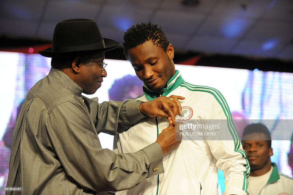 Nigerian President Goodluck Jonathan decorates the midfielder Mikel Obi (R) with national award during the presidential banquet in honour of the victorious team in Abuja February 12, 2013. The newly crowned African champions Nigerian Super Eagles arrives in Abuja to a warm reception by fans and government officials after defeating Burkina Faso to win the 2013 African Cup of Nations in South Africa.