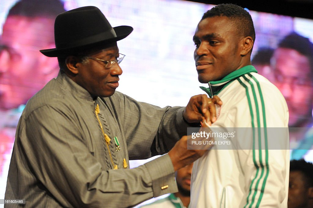 Nigerian President Goodluck Jonathan decorates the striker Emmanuel Emenike (R) with national award during the presidential banquet in honour of the victorious team in Abuja February 12, 2013. The newly crowned African champions Nigerian Super Eagles arrives in Abuja to a warm reception by fans and government officials after defeating Burkina Faso to win the 2013 African Cup of Nations in South Africa.