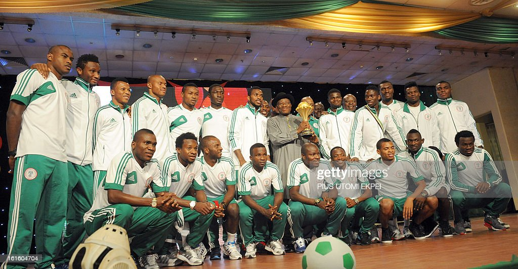 Nigerian President Goodluck Jonathan holds the trophy while posing with the victorious national football team of the 2013 African Cup of Nations during the presidential banquet in honour of the team in Abuja February 12, 2013. The newly crowned African champions Nigerian Super Eagles arrives in Abuja to a warm reception by fans and government officials after defeating Burkina Faso to win the 2013 African Cup of Nations in South Africa.