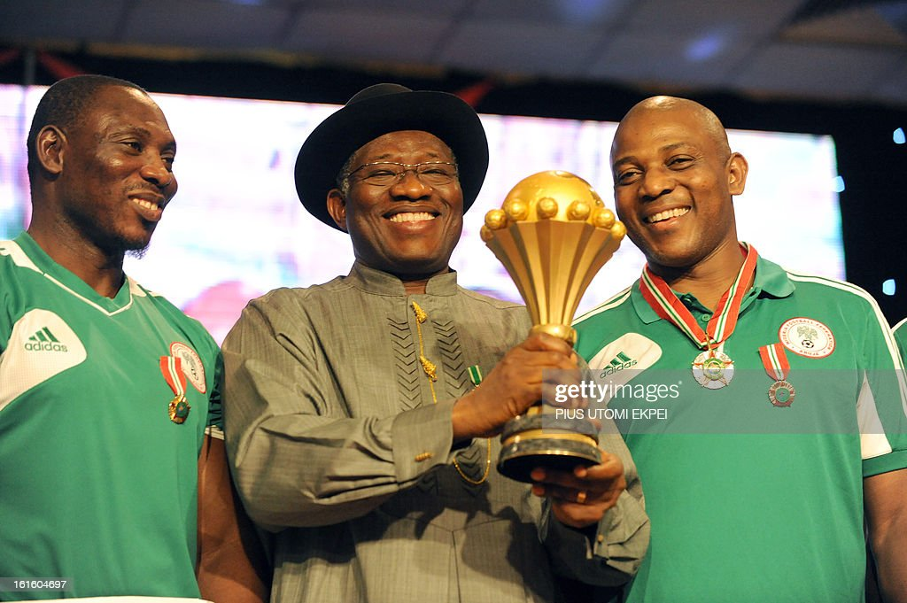 Nigerian President Goodluck Jonathan (C) is flanked by Coach Stephen Keshi (R) and Assistant Daniel Amokachi holds the trophy won by the national football team at the 2013 African Cup of Nations during the presidential banquet in honour of the victorious team in Abuja February 12, 2013. The newly crowned African champions Nigerian Super Eagles arrives in Abuja to a warm reception by fans and government officials after defeating Burkina Faso to win the 2013 African Cup of Nations in South Africa.