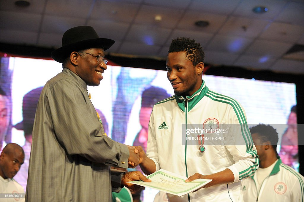 Nigerian President Goodluck Jonathan presents midfielder Mikel Obi (R) with national award during the presidential banquet in honour of the victorious team in Abuja February 12, 2013. The newly crowned African champions Nigerian Super Eagles arrives in Abuja to a warm reception by fans and government officials after defeating Burkina Faso to win the 2013 African Cup of Nations in South Africa. AFP PHOTO/PIUS UTOMI EKPEI