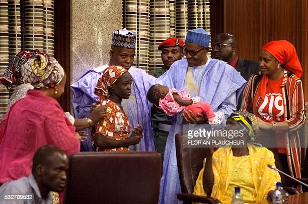 Nigerian President Mohammadu Buhari holds the daughter of the kidnapped Chibok schoolgirl Amina Ali as Borno state governor Kashim Shettima looks on...