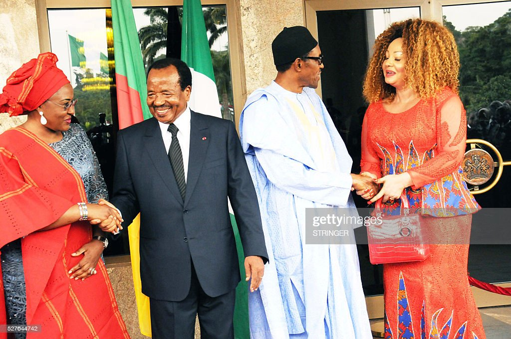 Nigerian President Mohammadu Buhari (2nd R) shakes hand with Cameroonian first lady Chantal Biya while Cameroonian president Paul Biya greets Nigerian first lady Aisha Buhari at the presidential Villa in Abuja, on May 3, 2016. Cameroonian President Paul Biya arrived accompanied by wife Chantal and senior government officials for a two-day state visit to Nigeria. / AFP / STRINGER