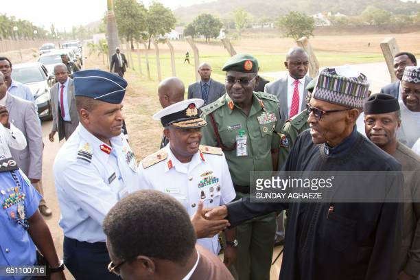 Nigerian President Mohammadu Buhari shakes hands with Airforce Chief Air Marshal Sadique Abubakar among other service chiefs upon his arrival at the...