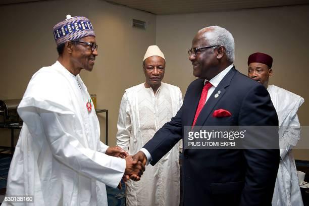 Nigerian President Muhammadu Buhari shakes hands with Sierra Leonean President Ernest Bai Koroma while Guinean President Alpha Conde and Nigerien...