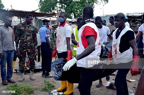 Nigerian RedCross workers carry a body away from the scene of an Improvised Explosive Device blast at Gomboru market in Maiduguri Borno State in...