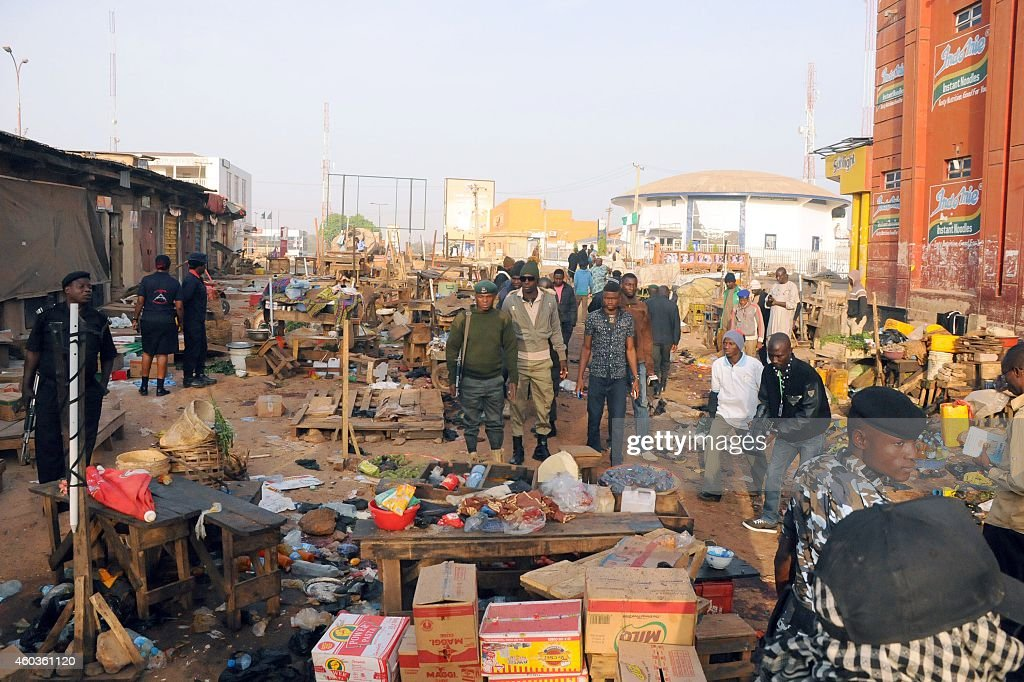Nigerian security inspect the scene of a bomb blast at the Jos Terminus Market on December 12 2014 A double bomb attack that killed 31 people in a...