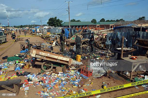 Nigerian security officers stand next to rubble in Kuje near Abuja on October 3 after two bomb blasts ripped through the outskirts of Nigeria's...