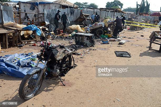 Nigerian security officers walk past burnt motorcycles and rubble in Kuje near Abuja on October 3 after two bomb blasts ripped through the outskirts...