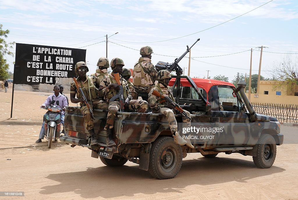 Nigerian soldiers ride a pickup truck on February 12, 2013 in the center of the northern Malian city of Gao, where the militant group Movement for Oneness and Jihad in West Africa (MUJAO) had controlled the city since June until the troops arrived in late January. African and French troops were on alert on February 12 after the MUJAO claimed a February 10 guerrilla attack and a pair of suicide bombings on February 8 and 9. Billboard reads: 'Enforcement of Sharia is the road to happiness.'