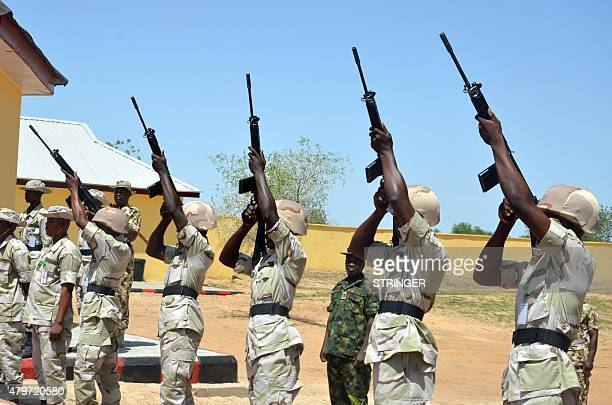 Nigerian soldiers shoot into the air during a ceremony to mark the release of suspected detainees cleared of being members of Boko Haram Islamists in...