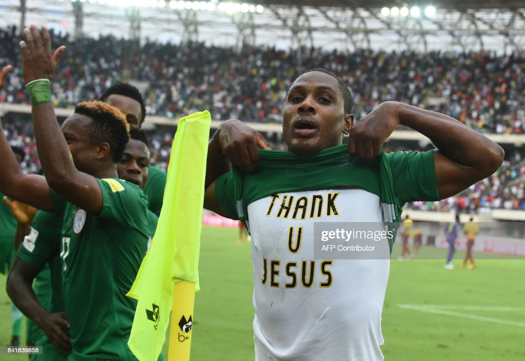 Nigerian striker Odion Ighalo pulls up his jersey to show his tshirt reading 'thank u Jesus' after scoring a goal against Cameroon during the 2018 FIFA World Cup qualifying football match between Nigeria and Cameroon at Godswill Akpabio International Stadium in Uyo, southern Nigeria, on September 1, 2017. /