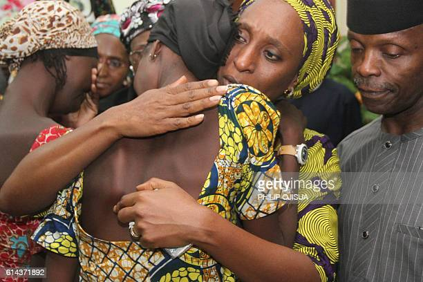 Nigerian Vice President Yemi Osinbajo looks on while his wife Dolapo comforts one of the 21 freed Chibok girls freed today from Boko Haram at his...
