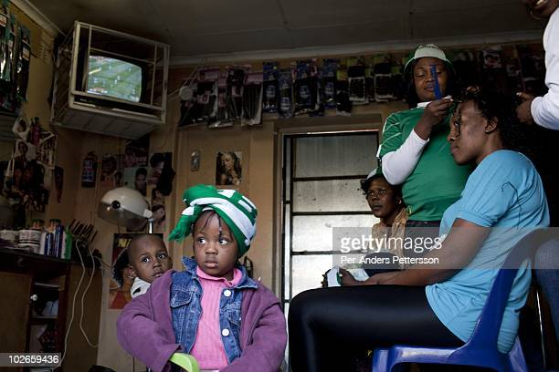 Nigerian women and children watch a soccer game between Nigeria and Argentina on June 12 2010 in a women's salon in Yeoville an immigrant suburb in...