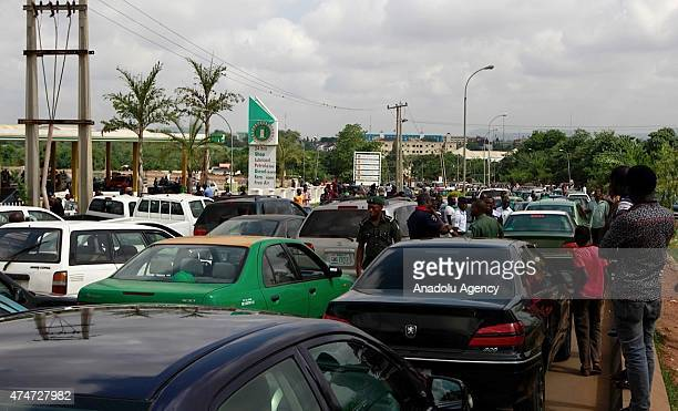 Nigerians queue with their cars to buy fuel at Mobil filling station in Abuja on May 21 2015 Long queues formed at petrol stations across oilrich...