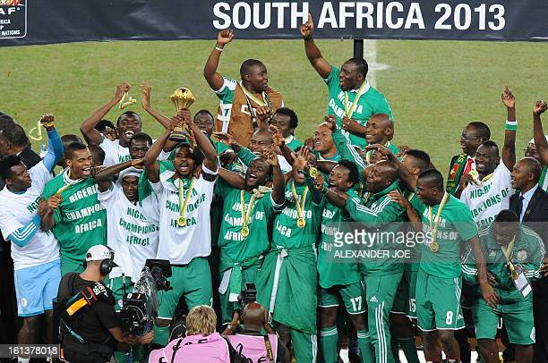 Nigeria's defender and team captain Joseph Yobo holds the trophy as he celebrates with his teammates winning the 2013 African Cup of Nations final...