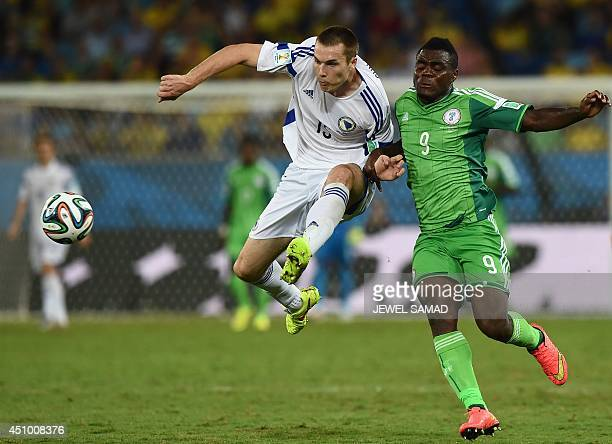 Nigeria's forward Emmanuel Emenike challenges BosniaHercegovina's defender Toni Sunjic during the Group F football match between Nigeria and...
