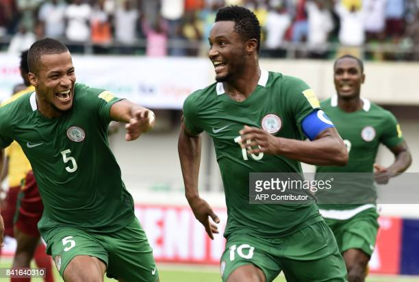 Nigeria's Mikel John Obi celebrates with teammates William Ekong and Odion Ighalo after scoring a goal during the 2018 FIFA World Cup qualifying...