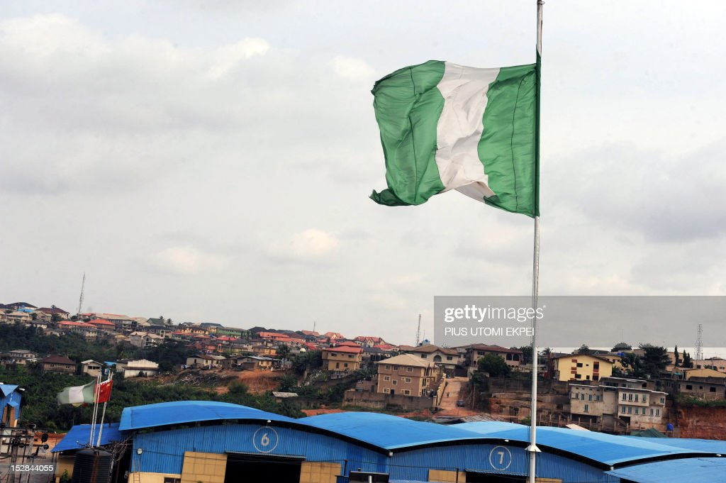 Nigeria's national flag flies above a factory on Ibadan expressway September 8, 2012 in Lagos. The flag designed by then student Michael Akinkunmi, was chosen in a competition held in1959 and officially hoisted on October 1, 1960 after Nigeria became independent from Britain. The green bands symbolise the land abundant with natural wealth of the country while the white band stands for unity and peace. AFP PHOTO/PIUS UTOMI EKPEI.