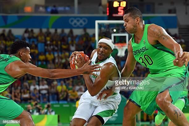 Nigeria's point guard Josh Akognon makes his way through Brazil's shooting guard Leandro Barbosa and Brazil's power forward Rafael Hettsheimeir...