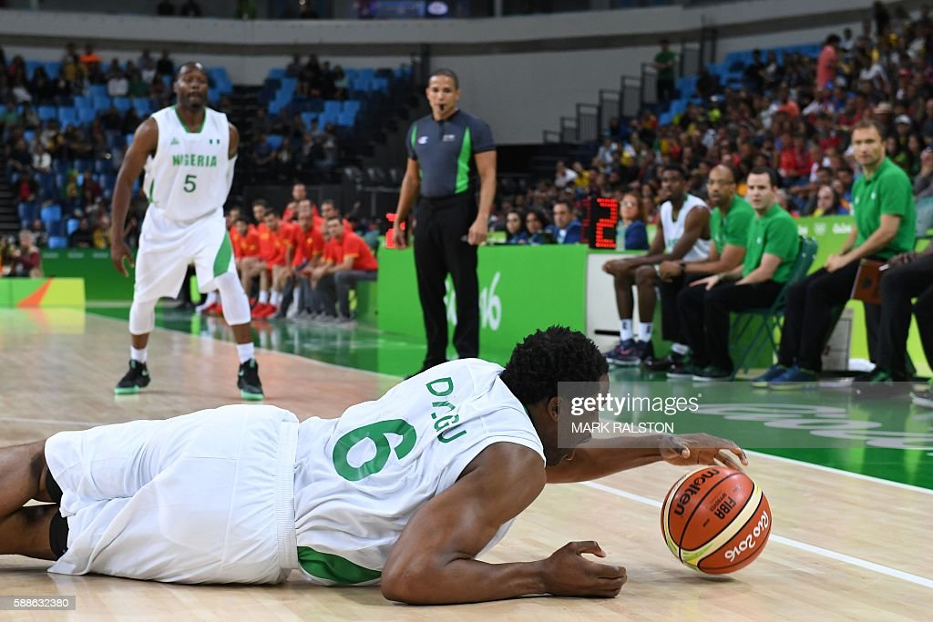 Nigeria's power forward Ike Diogu falls during a Men's round Group B basketball match between Nigeria and Spain at the Carioca Arena 1 in Rio de...