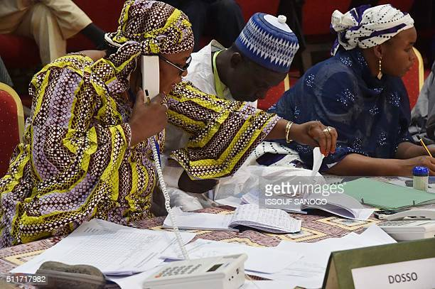 Niger's Commission electoral indenpendante members check the results of the presidential election on February 22 2016 at the palais des congres in...
