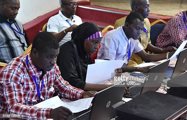 Niger's Independent Election Commission members check the results of the presidential elections on March 21 2016 at the Palais des Congres in Niamey...