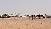 Niger's National Guard soldiers stand next to a Sukhoi SU25 ground attack jet and a Niger's Air Force Mi35P attack helicopter on the tarmac in Diffa...