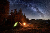 Night camping. Illuminated tent and campfire near forest under beautiful night sky full of stars and milky way
