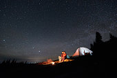 Night camping in the mountains. Couple tourists sitting at a campfire near illuminated tent under night starry sky. Long exprose