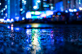 Night cityscape, colored lights reflected in the wet asphalt after rain. View from the level of asphalt, in blue tones