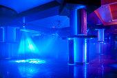 Disco club interior with disco lighting effects overlighting dance floor.