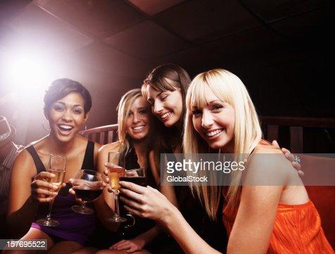 Night club - Smiling young female friends enjoying drinks