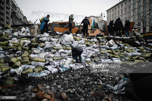 Night falls as antigovernment protesters rebuild barricades following continued clashes with police in Independence square despite a truce agreed...