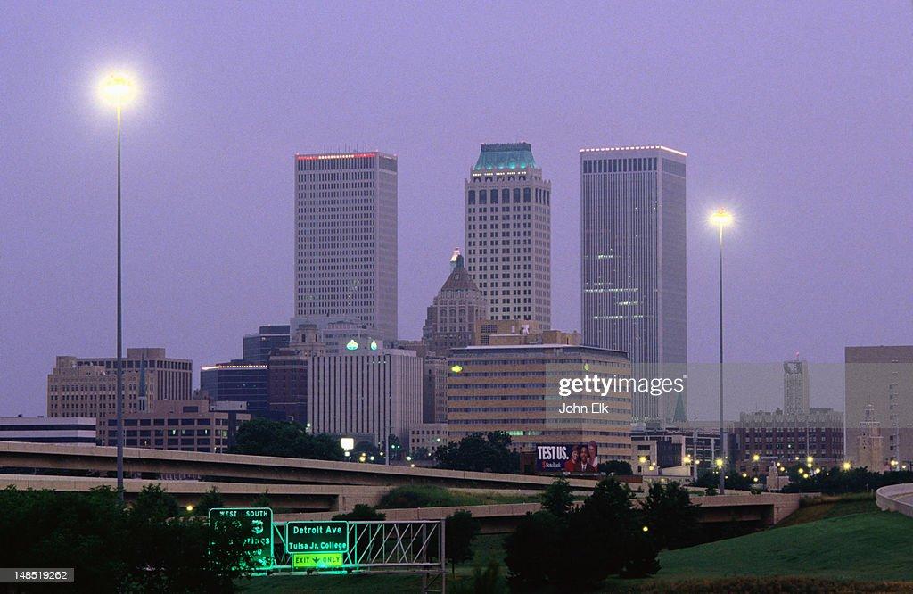 Night falls on city skyline.