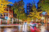 Night on the street in the old part of the big city with the lights of storefronts and shops, the blinding lights of car headlights and a paved roadway shimmering in neon lights after the last rain