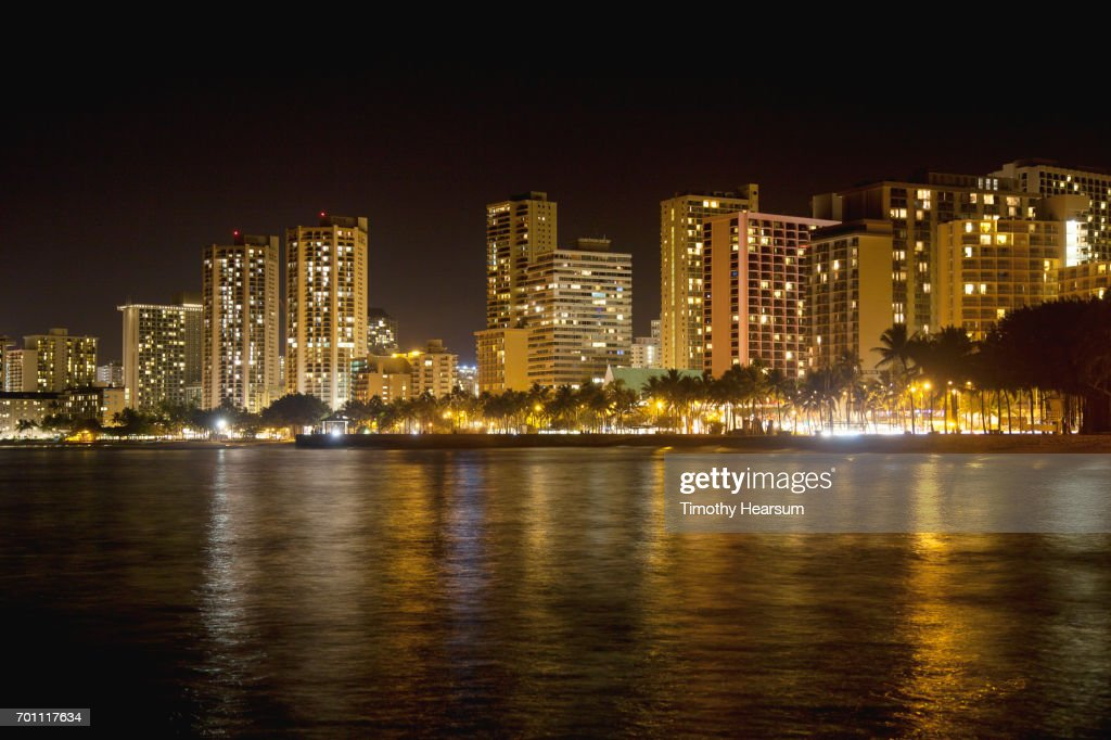 Night photo of lighted buildings and their reflections in water : Stock Photo