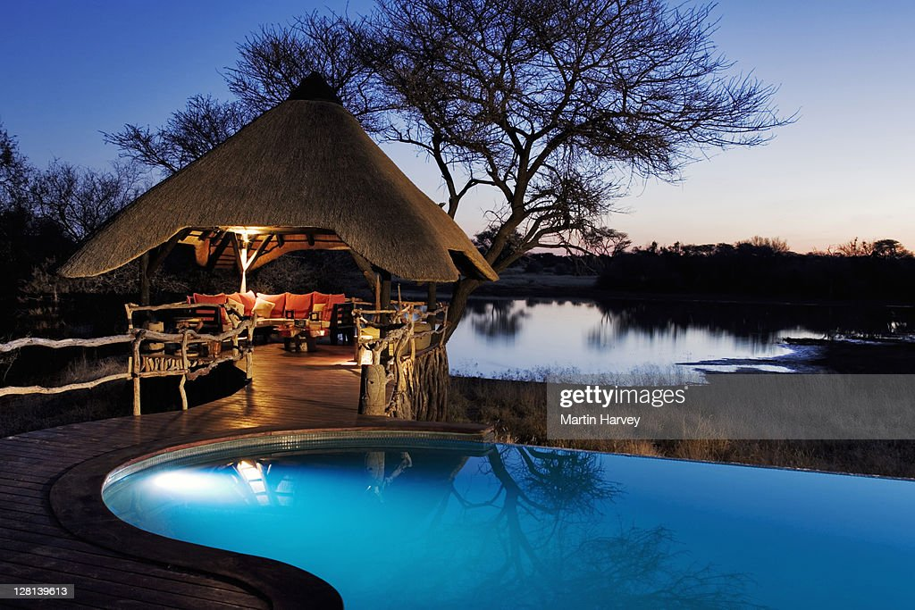 Night shot of the beautifully decorated lapa and swimming pool area at the Villa in Okonjima Private Game Reserve, Namibia. This luxury lodge offers guest the opportunity to view game drinking at the waterhole. (PR: Property Released) : Stock Photo