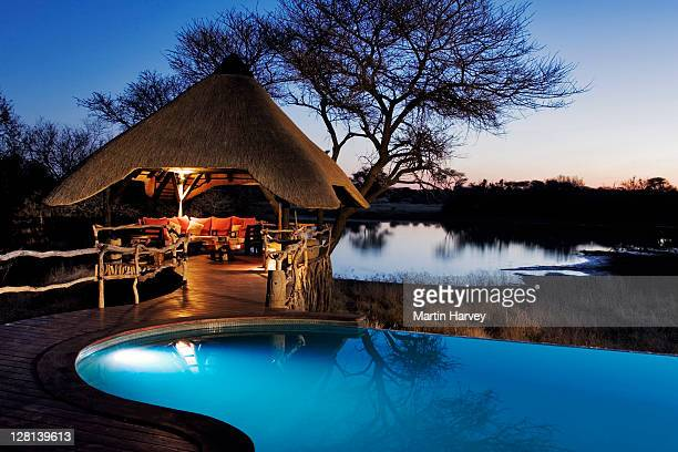 Night shot of the beautifully decorated lapa and swimming pool area at the Villa in Okonjima Private Game Reserve, Namibia. This luxury lodge offers guest the opportunity to view game drinking at the waterhole. (PR: Property Released)