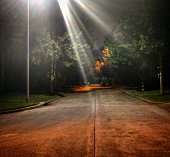 Beams of light from a tall streetlamp illuminate a dark suburban street in Clear Lake City, Houston, Texas.
